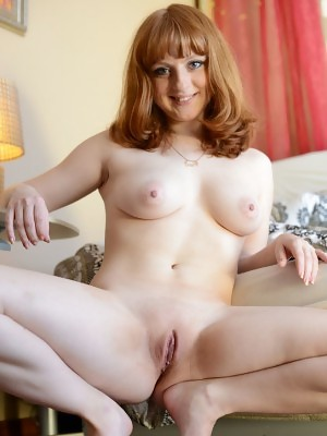 Redhead Kataly bares her luscious body as she poses on the sofa
