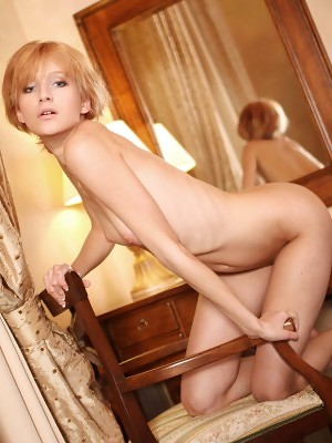 Mila F flaunts her petite body as she poses on the chair