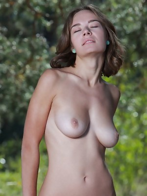 Selina playfully poses outdoors baring her beautiful tits