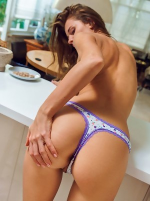 Kalisy strips her purple skirt baring her trimmed pussy in the kitchen